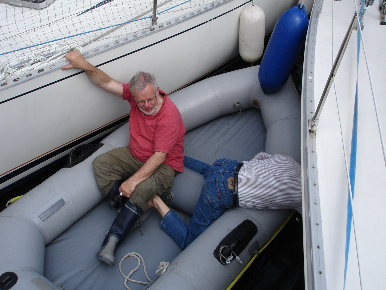 John L stailises the dinghy while John H tries to clear the blockage
